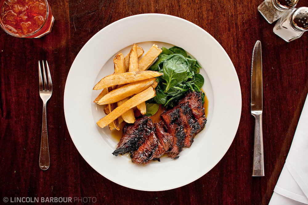 A top down view of a steak, french frieds, and sauteed spinach. A fork and knife to either side of the plate, salt and pepper shakers in the top right, and a reddish drink with ice in the top left.