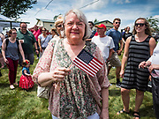 """04 JULY 2019 - INDIANOLA, IOWA: A woman with an American flag waits for Senator Kamala Harris (D-CA) before a campaign event in Indianola. Sen. Harris attended a """"house party"""" in Indianola as a part of her campaign to be the Democratic nominee for the US presidency in 2020. Iowa traditionally holds the first selection of the presidential election cycle. The Iowa caucuses are Feb. 3, 2020.      PHOTO BY JACK KURTZ"""