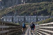 Male walkers cross Barmouth's pedestrian and rail bridge on the Mawddach Estuary, on 13th September 2018, in Barmouth, Gwynedd, Wales.