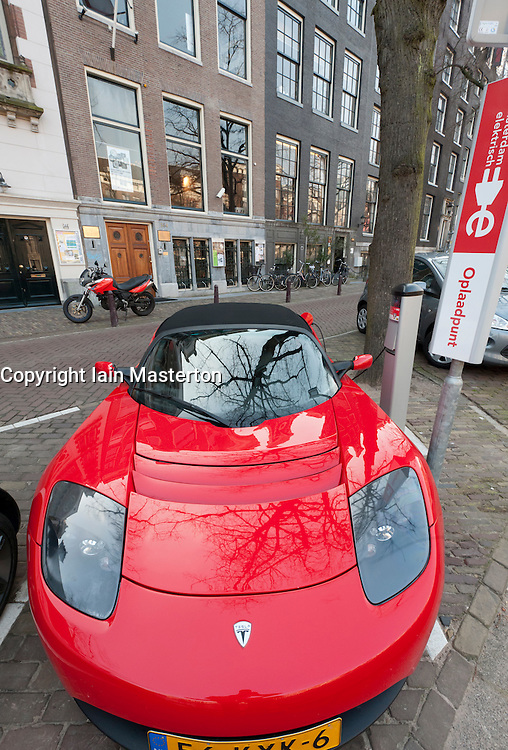 Electric Tesla sports car being recharged at public recharging point in Amsterdam The Netherlands