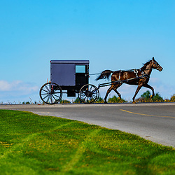 Intercourse, PA, USA - September 20, 2020: A silhouette view of an Amish buggy as it travels on a rural roadway in Lancaster County, PA.
