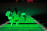 "Visitors, mostly curious tourists, walk down a flight of neon lit stairs near the artificial lake in Kangbashi New District of Ordos City, Inner Mongolia, China on 16 August, 2011. With an investment of over 161billion USD from the local government and revenue from the region's rich coal deposits, enough buildings have risen on the site of an old desert village to hold at least 300,000 residents, complete with ultra modern facilities and grand plazas. The district however is less than 10% occupied, dubbed the ""ghost city"", Kangbashi epitomizes China's real estate bubble and dangers in mindless investment fueled economic  growth. In 2011, the real estate price of Ordos city has dropped over 70%."