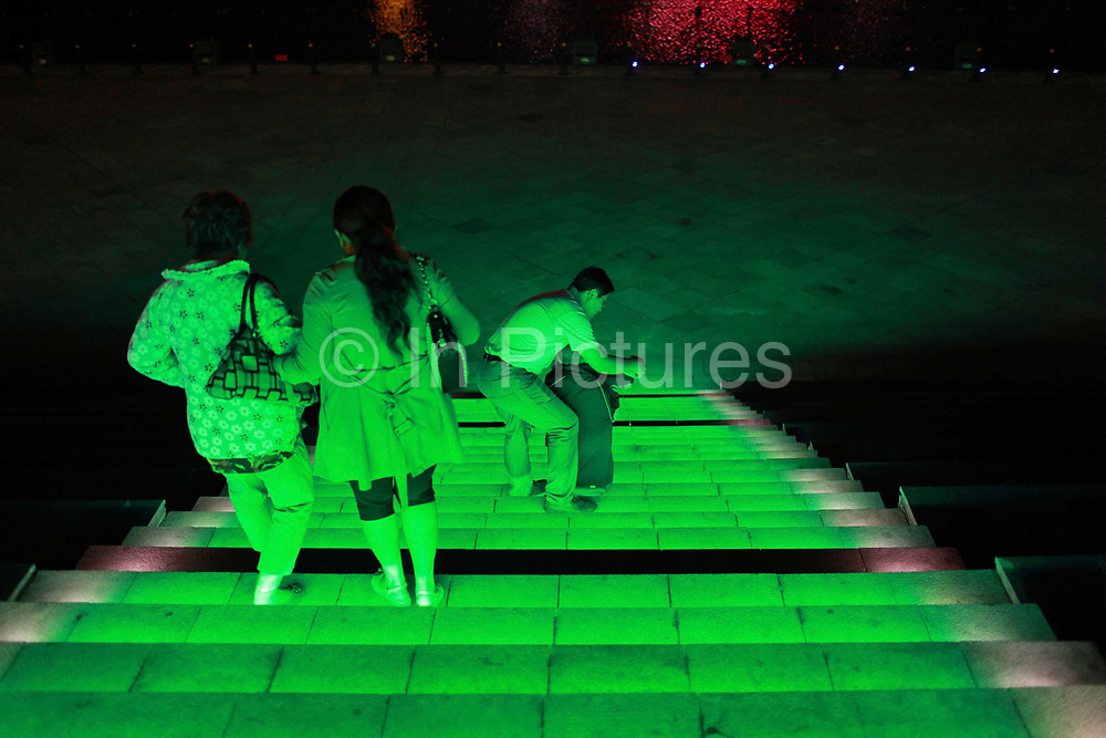 """Visitors, mostly curious tourists, walk down a flight of neon lit stairs near the artificial lake in Kangbashi New District of Ordos City, Inner Mongolia, China on 16 August, 2011. With an investment of over 161billion USD from the local government and revenue from the region's rich coal deposits, enough buildings have risen on the site of an old desert village to hold at least 300,000 residents, complete with ultra modern facilities and grand plazas. The district however is less than 10% occupied, dubbed the """"ghost city"""", Kangbashi epitomizes China's real estate bubble and dangers in mindless investment fueled economic  growth. In 2011, the real estate price of Ordos city has dropped over 70%."""