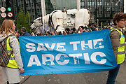 Two stewards hold a banner saying 'Save the Arctic' in front of Aurora, the double-decker-bus-size polar bear puppet specially commissioned by Greenpeace to lead an Arctic-inspired street parade to the London HQ of oil giant Shell on 15 September. The three-tonne marionette bear is operated from the inside by a team of 15 puppeteers,  and  hauled on ropes by 30 volunteers along a route from Victoria Gardens to Shell's HQ at Waterloo. The giant bear, which is made of replica and reclaimed ship parts as well as recycled materials, carries in her fur the names of over 3 and half million people who have joined the global movement to protect the Arctic from industrial exploitation. This parade  was part of a global day of action to protect the Arctic withtens of thousands of people taking to the streets in over 70 cities worldwide.