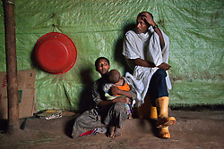 Fifteen-year-old Destaye and her husband Addisu, 27, sit in their home with their son near Bahir Dar, Ethiopia on Aug. 11, 2012. They divide their time between working in the fields and taking care of their 6-month-old baby. Like many other young couples, they tend to the domestic, economic and personal demands of being young parents. At the time of their marriage, when Destaye was age 11, she was still in school and her husband expressed interest in letting her continue her education. Since the birth of their son, however, she has had to confine her life exclusively to being a wife and mother.
