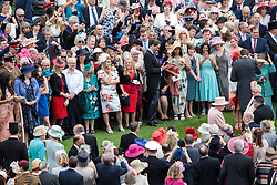 Queen Elizabeth II (centre right) greets guests at a garden party at Buckingham Palace in London.
