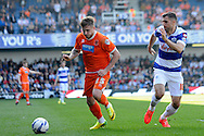 Blackpool's David Goodwillie running with the ball whilst Queens Park Rangers Aaron Hughes trying to keep pace. Skybet football league championship match , Queens Park Rangers v Blackpool at Loftus Road in London  on Saturday 29th March 2014.<br /> pic by John Fletcher, Andrew Orchard sports photography.
