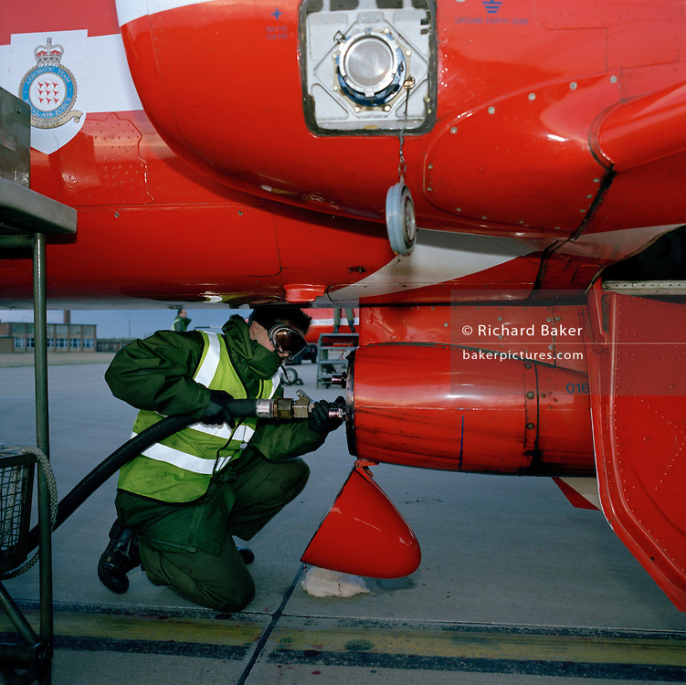 A Dye Team engineer refills the dye-derv mixture to a Hawk jet of the Red Arrows, Britain's RAF aerobatic team.
