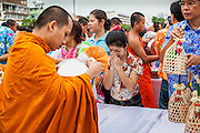 13 APRIL 2013 - BANGKOK, THAILAND:  People present alms to monks during a Songkran merit making ceremony at Bangkok City Hall. Songkran is the traditional Thai New Year's Festival. It is held April 13-16. Many Thais mark the holiday by going to temples and making merit by giving extra alms to monks or offering extra prayers. They also mark Songkran with joyous water fights. Songkran has been a national holiday since 1940, when Thailand moved the first day of the year to January 1.   PHOTO BY JACK KURTZ