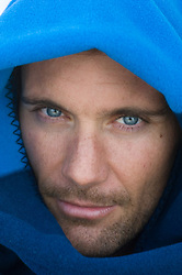 headshot of a man with blue eyes with a blue blanket wrapped around his head