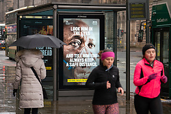 Edinburgh, Scotland, UK. 27 January 2020. Members of the public walk past new Government Covid-19 health warning display posters on Princes street in Edinburgh today. Iain Masterton/Alamy Live News