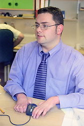 Man with disability; who is wheelchair user; working at desk in office using computer mouse,