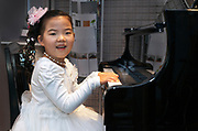 happy smiling little girl playing a grand piano