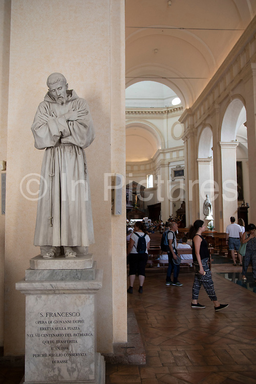 Interior with a statue of St Francis of Assisi in the Cathedral of San Rufino in Assisi, Umbria, Italy. In this church Saint Francis of Assisi, Saint Clare, and many of their original disciples were baptised. Assisi is a town in the Province of Perugia in the Umbria region, on the western flank of Monte Subasio. It is generally regarded as the birthplace of the Latin poet Propertius, and is the birthplace of St. Francis, who founded the Franciscan religious order in the town in 1208, and St. Clare, Chiara dOffreducci, the founder of the Poor Sisters, which later became the Order of Poor Clares after her death. Assisi is now a major tourist destination for those sightseeing or for more religious reasons.