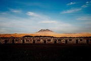 The remains of Buenaventur mining town in the higlands near the border with Bolivia, and Aucanquilcha volcano in the background. All the Atacama desert is littered with abandoned mining towns. November 2009.