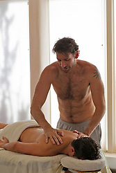 shirtless man giving a massage to another man