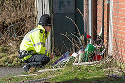 © Licensed to London News Pictures . 16/02/2014 . Oldham , UK . A police officer looks at flowers and tributes left behind terraces parallel to Ripponden Road after the body of fifteen year old Leon Cudworth was discovered in the early hours of 15th Februrary 2014 . Photo credit : Joel Goodman/LNP