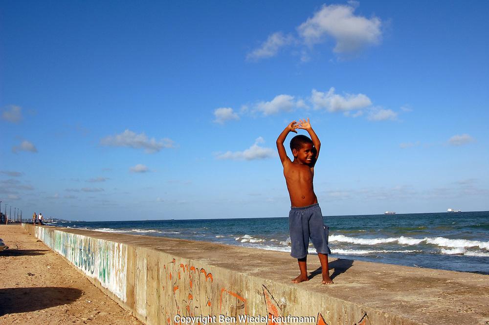Young child walking along coast Recife Brazil