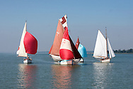Gaffers race down the River Stour in Essex under full sail in light airs