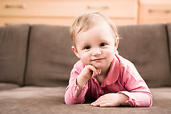 Portrait baby girl 18 months old lying on sofa