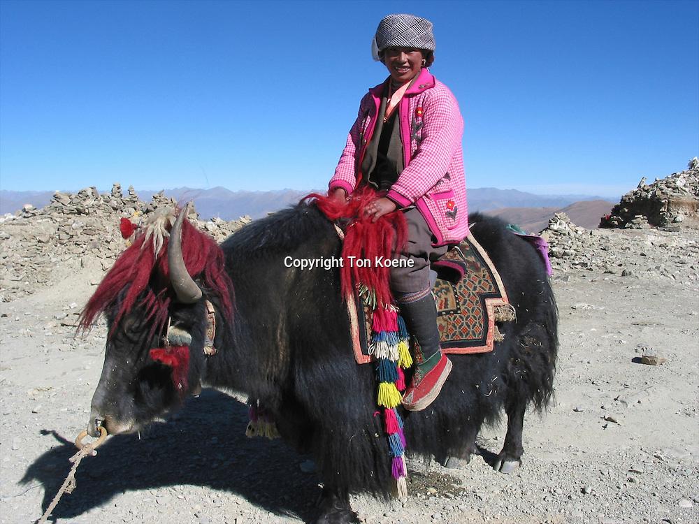 A woman sitting on her yak in Tibet