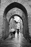 Pedestrians pass beneath the arched city walls of San Gimignano, Tuscany, Italy. Also available in full color.