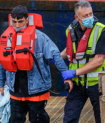 © Licensed to London News Pictures. 10/07/2021. Dover, UK. A migrant is brought ashore by a Border Force officer at Dover Harbour in Kent after crossing the English Channel. Photo credit: Stuart Brock/LNP