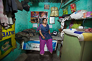 An Operation Asha counsellor sits intside a health clinic as Tuberculosis (TB) patients arrive in Tehkhand Slum, Delhi, India.  This clinic dispenses free TB medication provided by the government.  The treatment for TB is a minimum 6 month course of combination antibiotics that must been taken everyday, otherwise fatal drug resistance can develop. TB is an infectious disease and a huge public health issue often associated with poverty.  TB is completely curable, however TB rates are increasing and India suffers from the highest burden of TB in the world.