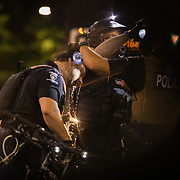 CHARLOTTE, NC - August 24:  An officer with the Charlotte-Mecklenburg police is attended to after being overcome by another officers pepper spray during a protest with people organized by Charlotte Uprising for a third night in a row as they march through uptown Charlotte near the site of the 2020 Republican National Convention in uptown Charlotte on August 24, 2020. The group, organized by Charlotte Uprising is protesting the existence of the convention in Charlotte, the policies of the Trump administration and the the abolishment of police and prisons. Delegates are holding private meetings inside the convention center ahead of the official start of the paired down convention on August 24th. (Photo by Logan Cyrus for AFP)