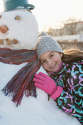 Portrait of girl leaning on snowman in winter