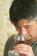 Didier Chadourne winemaker and manager tasting his wine in a glass inscribed with the name of the chateau  Chateau Potensac Cru Bourgeois Ordonnac  Medoc  Bordeaux Gironde Aquitaine France
