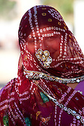 Pretty young Indian woman modestly veiled in Narlai village in Rajasthan, Northern India