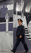 """Moscow, Russia, 20/06/2010..A policeman walks past murals depicting Raskolnikov's double murder and Svidrigailov's suicide in Crime & Punishment at the just-opened Dostoevsky metro station, the newest in Moscow's underground metro system. The station's opening was delayed by several weeks after psychiatrists claimed the gloomy and violent images in murals depicting scenes from Dostoevsky's novels would make the station a """"mecca for suicides""""."""
