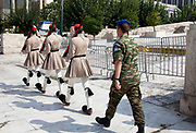 "Changing the Guard (often incorrectly referred to as the Changing of the Guard), refers to a formal ceremony in which sentries providing ceremonial guard duties at important institutions are relieved by a new batch of sentries. The ceremonies are often elaborate and precisely choreographed. In the state capital, Athens, members of the elite Evzones light infantry unit, provide a 24-hour honor guard, with an hourly guard change, at the Presidential Mansion and at the Tomb of the Unknown Soldier, off Syntagma Square at the foot of the Hellenic Parliament. The Changing the Guard at the Tomb of the Unknown Soldier in particular has become a tourist attraction, with many people marvelling at the guards, who stand motionless for two 20-minute intervals, during their 1 hour shifts. Greek soldiers called ""Evzons"" or 'Tsoliades' in their traditional pleated skirt uniform and shoes with toes tipped by a red or black ball called a 'foonda' are who guard the tomb. Athens is the capital and largest city of Greece. It dominates the Attica periphery and is one of the world's oldest cities, as its recorded history spans around 3,400 years. Classical Athens was a powerful city-state. A centre for the arts, learning and philosophy."