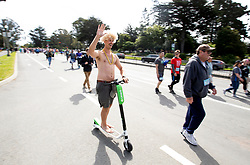 A man rides a scooter through Golden Gate Park at the 107th running of the Bay to Breakers, Sunday, May 20, 2018, in San Francisco. (Photo by D. Ross Cameron)