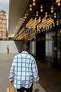 Seen from the rear, a man wearing a chequed shirt walks beneath lighting of the Odeon Leicester Square cinema, on 29th April 2019, in London, England.