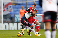 Crawley Town's Jordan Tunnicliffe and Bolton Wanderers Nathan Delfouneso(7) contest a loose ball  during the EFL Sky Bet League 2 match between Bolton Wanderers and Crawley Town at the University of  Bolton Stadium, Bolton, England on 2 January 2021.
