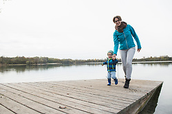 Mother and son walking on wooden jetty over lake