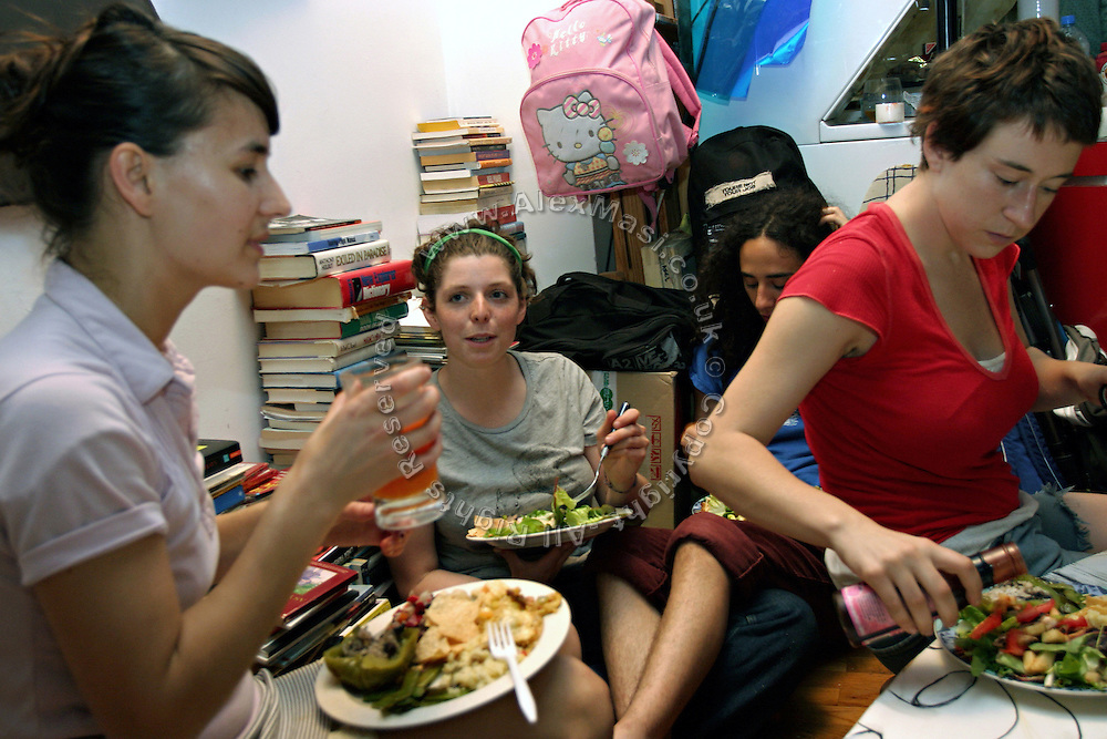 Stephanie, 21, (left) Rachel, 22, (centre left) and other two members of the Freegan community enjoying a dinner cooked entirely with food recovered from dumping sites around the island of Manhattan, New York, NY., on Friday, June 23, 2006. Freegans are a community of people who aims at recovering wasted food, books, clothing, office supplies and other items from the refuse of retail stores, frequently discarded in brand new condition. They recover goods not for profit, but to serve their own immediate needs and to share freely with others. According to a study by a USDA-commissioned study by Dr. Timothy Jones at the University of Arizona, half of all food in the United States is wasted at a cost of $100 billion dollars every year. Yet 4.4 million people in the United States alone are classified by the USDA as hungry. Global estimates place the annual rate of starvation deaths at well over 8 million. The massive waste generated in the process fills landfills and consumes land as new landfills are built. This waste stream also pollutes the environment, damages public health as landfills chemicals leak into the ground, and incinerators spew heavy metals back into the atmosphere. Freegans practice strategies for everyday living based on sharing resources, minimizing the detrimental impact of our consumption, and reducing and recovering waste and independence from the profit-driven economy. They are dismayed by the social and ecological costs of an economic model where only profit is valued, at the expense of the environment. In a society that worships competition and self-interest, Freegans advocate living ethical, free, and happy lives centred around community and the notion that a healthy society must function on interdependence. Freegans also believe that people have a right and responsibility to take back control of their time.