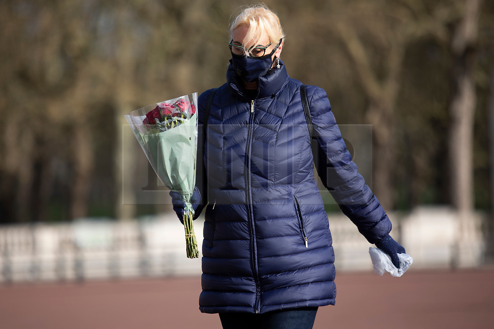 © Licensed to London News Pictures.11/04/2021. London, UK. A woman prepares to place flowers outside Buckingham Palace. On Friday the 9th of April Buckingham Palace announced that Prince Philip The Duke of Edinburgh passed away in the morning at Windsor Castle . Photo credit: George Cracknell Wright/LNP