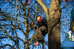 Harefield, UK. 21 January, 2020. An activist puts his boots on whilst suspended from a tree at the Save the Colne Valley wildlife protection camp. Activists seeking to protect ancient woodland threatened by the HS2 high-speed rail link continue to occupy both the roadside and woodland sites of the camp having retaken it from bailiffs acting on behalf of HS2 on 18th January. 108 ancient woodlands are set to be destroyed by HS2.