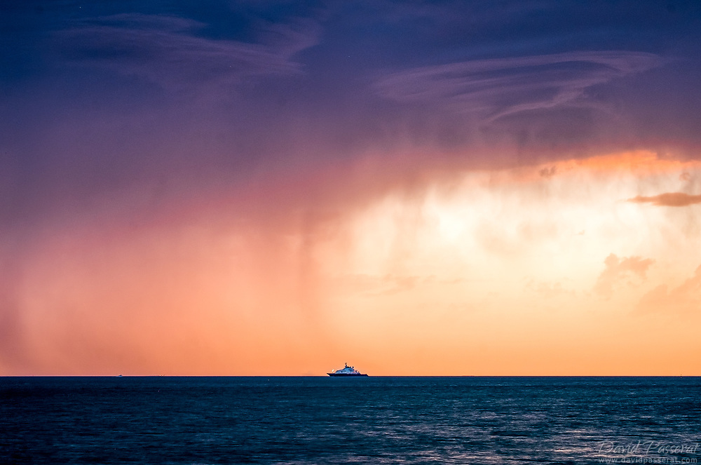 Approaching storm over the sea and distant boat.