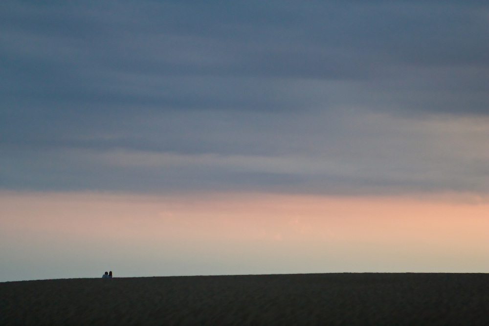 A couple reclines on the sand dunes beneath a rose and blue sky.