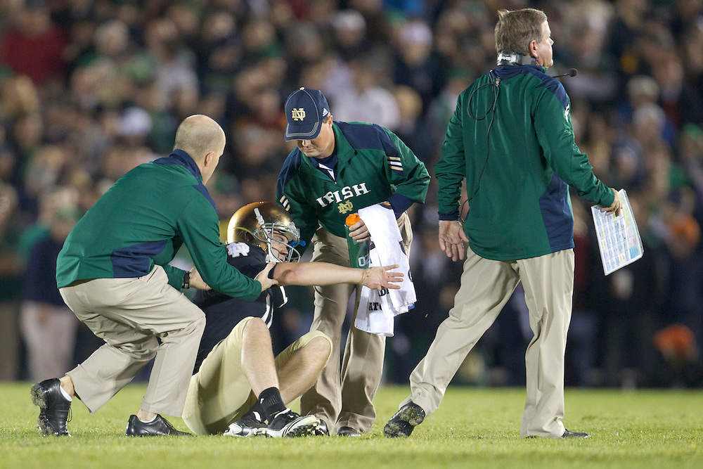 Notre Dame quarterback Tommy Rees (#11) is helped up by trainers during third quarter of NCAA football game between Notre Dame and USC.  The USC Trojans defeated the Notre Dame Fighting Irish 31-17 in game at Notre Dame Stadium in South Bend, Indiana.