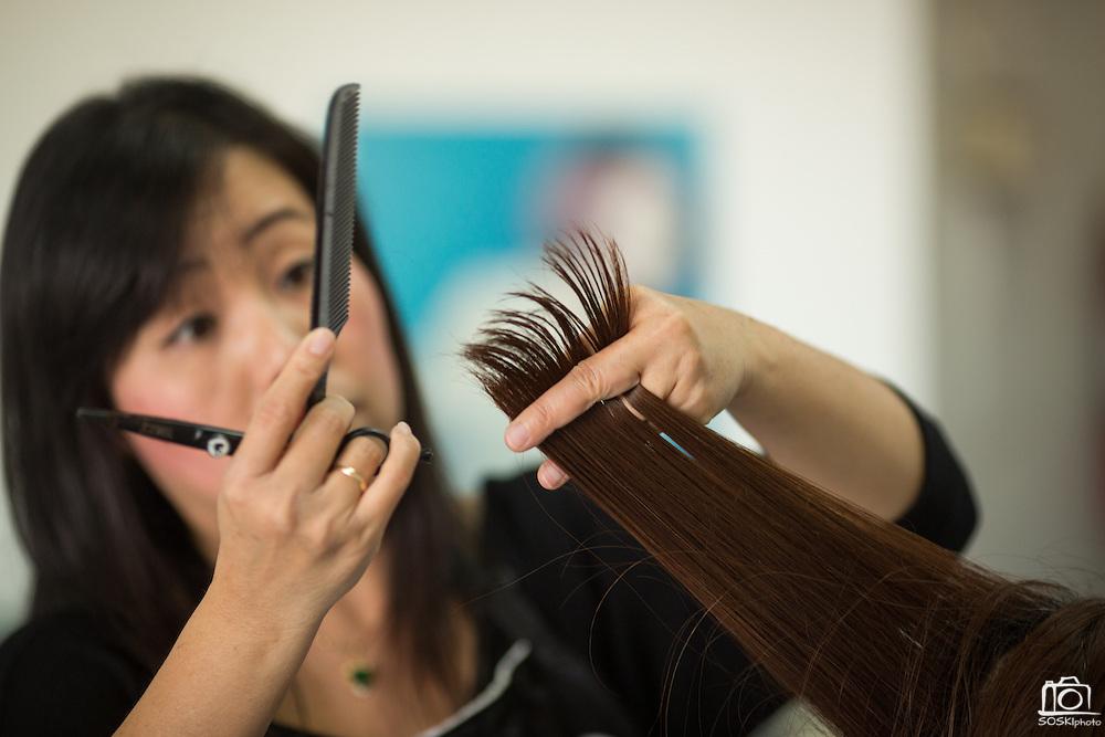 Hue Luu cuts a customer's hair at Tina's Hair Design in Milpitas, California, on September 11, 2014. (Stan Olszewski/SOSKIphoto)