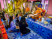 "24 JUNE 2017 - BANG KRUAI, NONTHABURI: A Buddhist monk talks to people after a rebirthing ceremony at Wat Ta Kien (also spelled Wat Tahkian), a Buddhist temple in the suburbs of Bangkok. People go to the temple to participate in a ""Resurrection Ceremony."" Thai Buddhists believe that connecting people by strings around their heads, which are connected to a web of strings suspended from the ceiling, amplifies the power of the prayer. Groups of people meet and pray with the temple's Buddhist monks. Then they lie in coffins, the monks pull a pink sheet over them, symbolizing their ritualistic death. The sheet is then pulled back, and people sit up in the coffin, symbolizing their ritualist rebirth. The ceremony is supposed to expunge bad karma and bad luck from a person's life and also get people used to the idea of the inevitability of death. Most times, one person lays in one coffin, but there is family sized coffin that can accommodate up to six people. The temple has been doing the resurrection ceremonies for about nine years.     PHOTO BY JACK KURTZ"