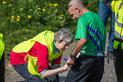 Maidenhead, UK. 19th April, 2019. Prime Minister Theresa May signs an autograph while serving as a marshal at the annual Maidenhead Easter 10 charity race on Good Friday.