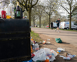 © Licensed to London News Pictures. 31/03/2021. London, UK. A man jogs past an overflowing bin in Greenwich Park after hundreds of people visited the park to enjoy sunny weather and take advantage of new lockdown rules that allow groups of six to meet outside. Photo credit: George Cracknell Wright/LNP