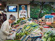 "29 FEBRUARY 2020 - ST. PAUL, MINNESOTA: A woman sets up her vegetable stand in the produce market in the Hmong Village. A portrait of Gen. Vang Pao dominates the room. Vang Pao was a Hmong militay leader who led the Hmong army in the ""Secret War"" in Laos, when the Hmong were allied with the US against the North Vietnamese. Thousands of Hmong people, originally from the mountains of central Laos, settled in the Twin Cities in the late 1970s and early 1980s. Most were refugees displaced by the American war in Southeast Asia. According to the 2010 U.S. Census, there are now 66,000 ethnic Hmong in the Minneapolis-St. Paul area, making it the largest urban Hmong population in the world. Hmong Village, the largest retail and restaurant complex that serves the Hmong community, has more than 250 shops and 17 restaurants.   PHOTO BY JACK KURTZ"