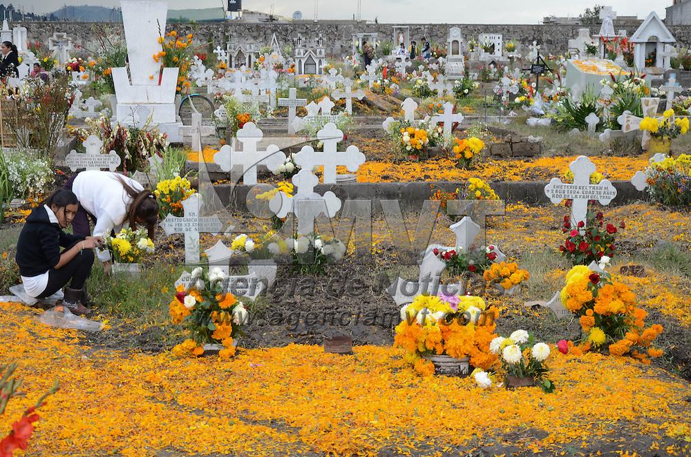 Toluca, México.- Familias pertenecientes a las comunidades en San Cristobal Huichochitlán y San Pablo Autopan celebran a San Miguel Arcángel alfombrando con flor de cempasuchil las tumbas de sus queridos. Agencia MVT / Arturo Hernández.